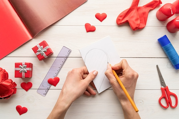 Valentines day craft diy. step by step instruction making paper heart shape hot air balloon. step 1 - fold paper and draw a half of a heart