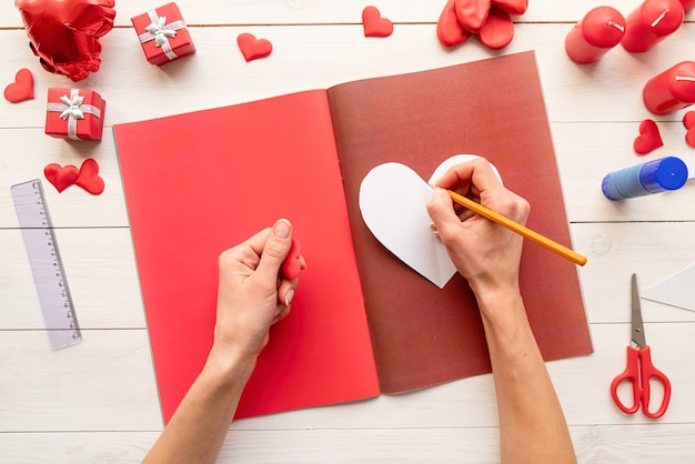Valentines day craft diy. step by step instruction making paper heart shape hot air balloon. step 3 - use the heart template to draw three hearts on colored paper Premium Photo