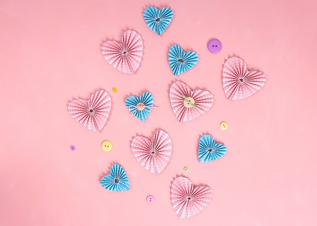 Valentines day craft. paper hearts in the pink background.