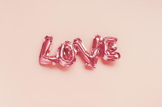 발렌타인 데이 창조적 인 개념. 풍선 핑크 광택 호일 풍선 모양의 분홍색 배경에 단어 사랑.