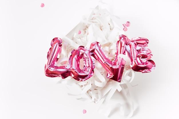 발렌타인 데이 창조적 인 개념. 풍선 핑크 광택 호 일 풍선 단어 기호 흰색 배경에 고립 된 현재 선물 상자에 사랑. 평면 평면도 복사 공간이 있습니다. 가볍고 밝은 구성