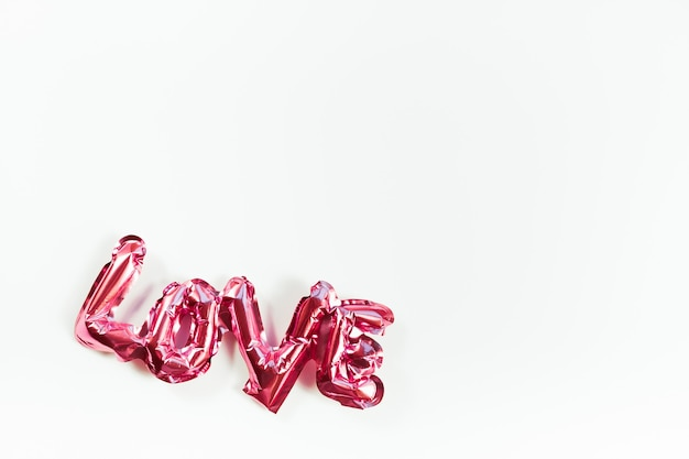 Valentines day creative concept. inflatable pink glossy foil balloon word sign love with shadows isolated on white background. top view flat lay with copy space. light and bright composition