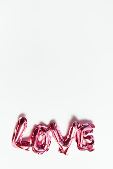 Valentines day creative concept. inflatable pink glossy foil balloon word sign love with shadows isolated on white background.