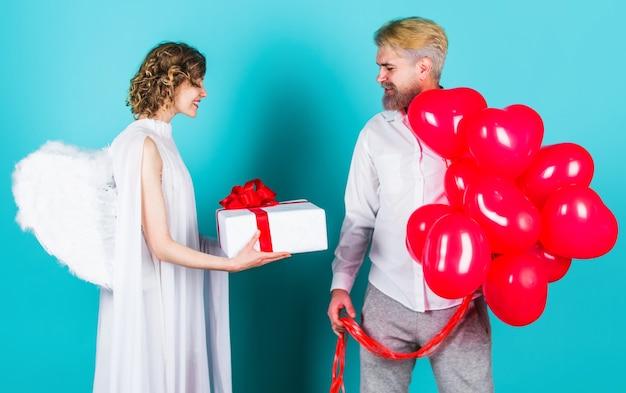 バレンタイン・デー。プレゼントと風船を持つキューピッドの天使。バレンタインデーのカップル。素敵なカップル。