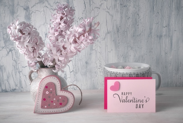 Valentines day decorations, white desk organizer with wooden calendar, cup of hot chocolate and pink hyacinth flowers