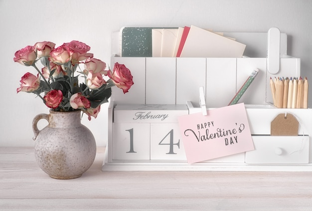 Valentines day decorations, white desk organizer with wooden calendar, cup of hot chocolate and pink roses.