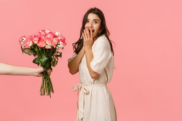 Valentines day, delivery and beauty concept. amazed woman gasping and surprised as someone giving her beautiful bouquet flowers, congratulations with anniversary, pink wall