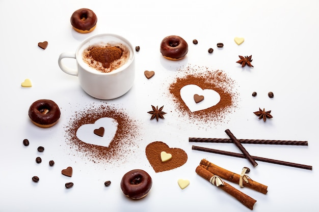 Valentines day design concept with cocoa powder in the shape of heart, chocolate doughnuts and cappuccino
