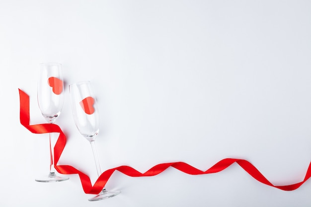 Valentines day dinner romantic festive setting, red tape, champagne wine glass, bottle, hearts on white wooden background. copy space, place for text. top view.