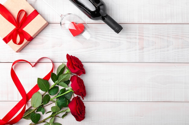 Valentines day dinner romantic setting, red tape, kraft gift box, heart in wine glass, bottle, roses, on white wooden background. copy space, place for text. top view, flat lay, horizontal.