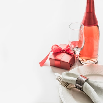 Valentines day dinner with table place setting with red gift, a bottle of champagne on white. close up. valentine's card.