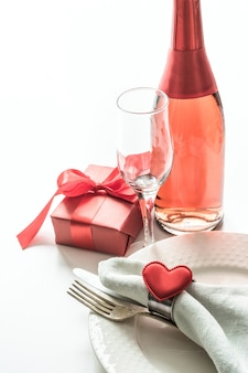 Valentines day dinner with table place setting with red gift, glass for champagne, a bottle of champagne, heart ornaments with silverware on white. close up. valentine's card.