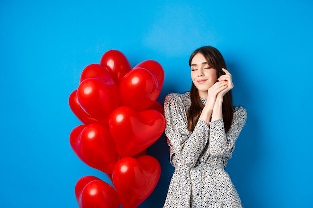 День святого валентина. мечтательная романтическая женщина закрыла глаза и представляла себе прекрасное свидание, стоя возле сердечных шаров и улыбаясь, синий фон.
