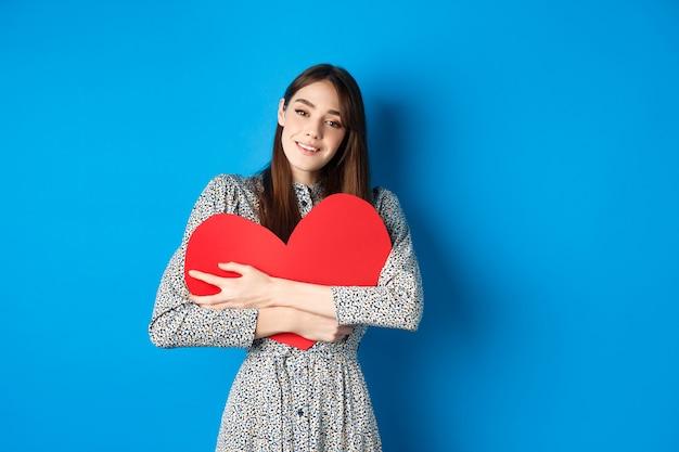 발렌타인 데이 꿈꾸는 낭만적 인 여성이 카메라 서에서 관능적 인 찾고 큰 붉은 심장 컷 아웃을 껴안고...