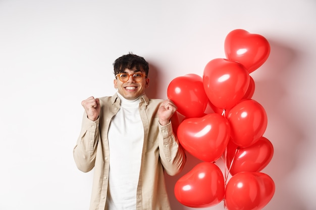 Valentines day. excited smiling man eager to go on date, celebrating with lover, standing near red hears balloons, white background.