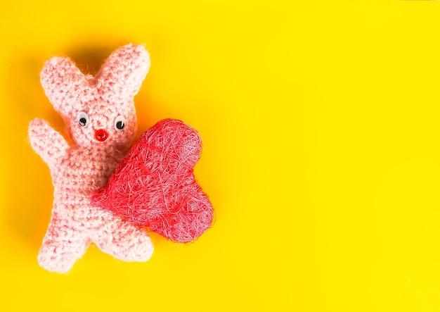 뜨개질을 한 수제 장난감 토끼와 장식용 하트가 있는 발렌타인 데이 축제 카드.