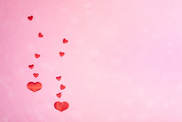 Valentines day festive pink background with hearts bokeh and red hearts on it. space.