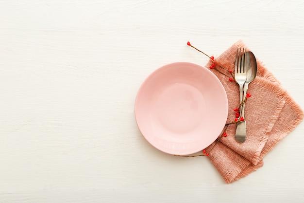 Сервировка праздничного стола дня святого валентина на белом деревянном столе. ужин в ресторане на день святого валентина. два красных сердца на розовой пластине. день святого валентина, любовь, романтика, концепция знакомств, копия пространства, плоская планировка