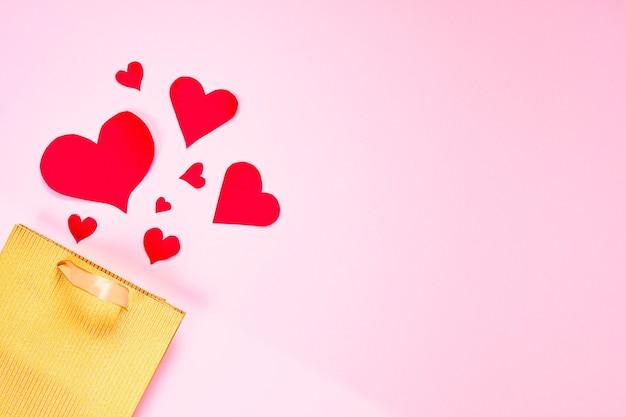 День святого валентина квартира лежала копия пространства. золотой бумажный подарочный пакет и красные сердца на розовом бумажном фоне.