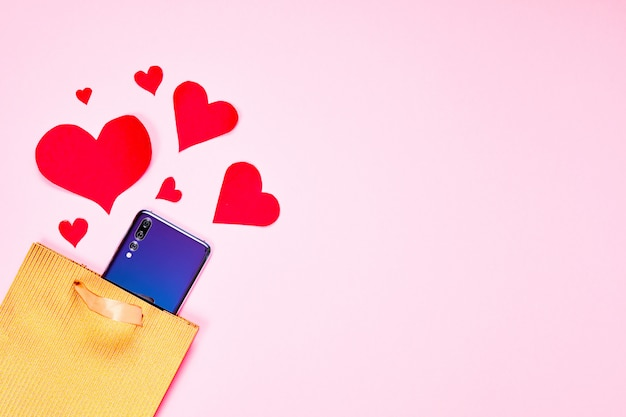 Valentines day flat lay copy space. golden paper gift bag, smartphone and red hearts on pink paper background.