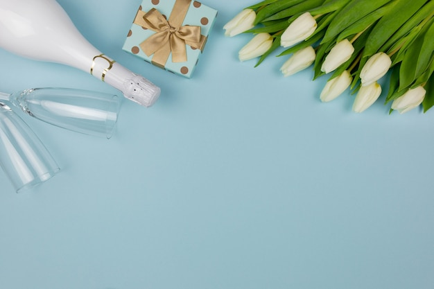 Valentines day flat lay with champagne, gift box and white tulips flowers bouquet on blue.