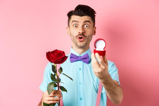 День святого валентина. забавный человек с усами и галстуком-бабочкой делает предложение, показывает обручальное кольцо и делает предложение