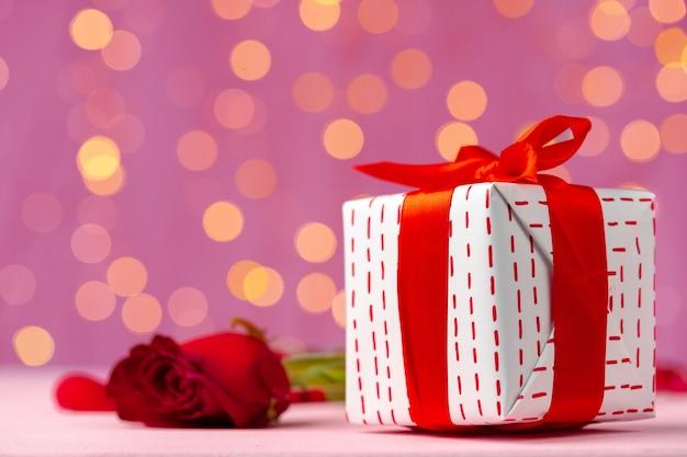 バレンタインデーの贈り物と木製のテーブルの上のバラのクローズアップ