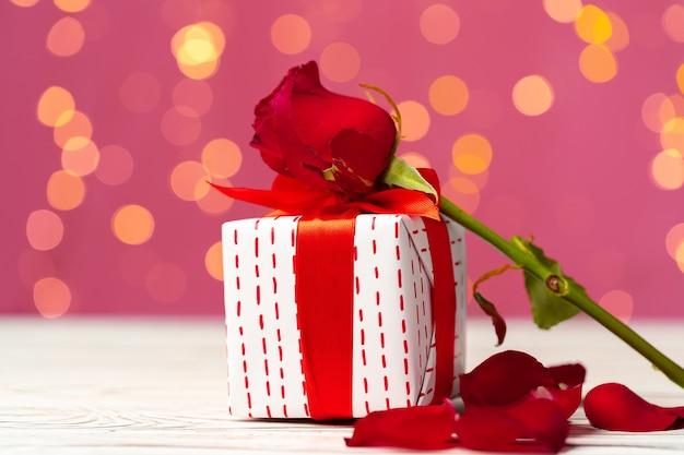 バレンタインデーの贈り物と木製のテーブルの上のバラ