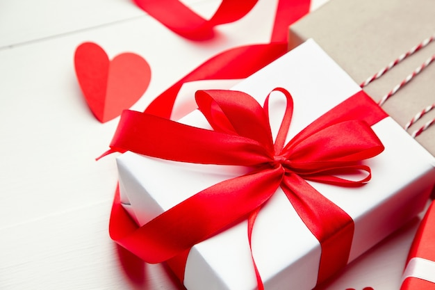 Подарочная коробка на день святого валентина и красное бумажное сердце на белом деревянном фоне
