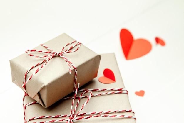 Подарочная коробка на день святого валентина и сердечки из красной бумаги на белом фоне