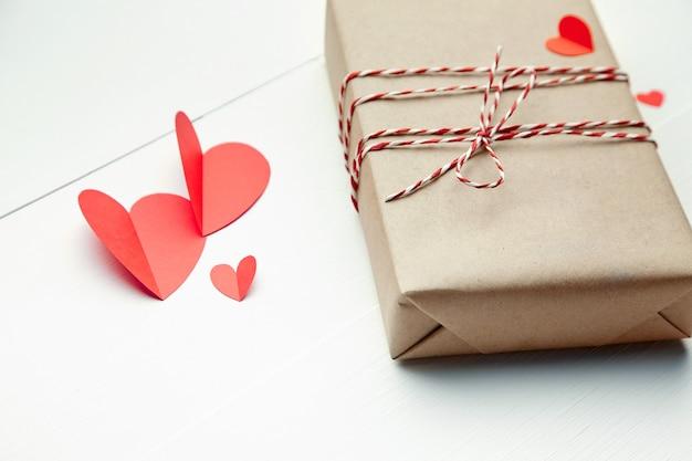 Подарочная коробка на день святого валентина и красные бумажные сердца на белом деревянном столе