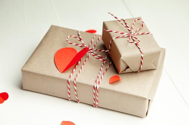Подарочная коробка на день святого валентина и красные бумажные сердца на белом
