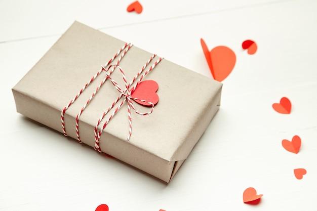 Подарочная коробка на день святого валентина, украшенная красными сердечками на белом деревянном столе