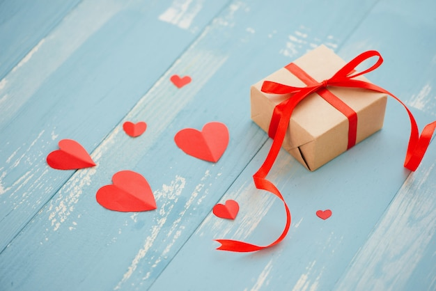バレンタイン・デー。ギフト用の箱、紙のハート、青い背景の上面に紙吹雪