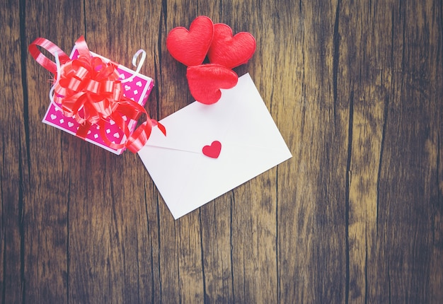 Valentines day gift box pink on wood envelope love mail valentine letter card with red heart love concept