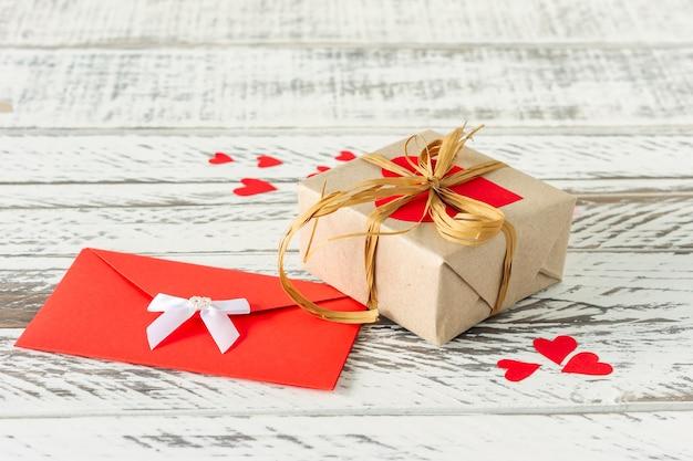 愛の手紙、木製の背景に紙のハートの封筒とバレンタインデーのギフトボックス。バレンタインデーや誕生日のグリーティングカード。