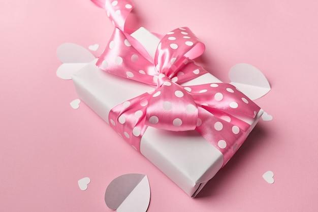 Подарочная коробка на день святого валентина с бумажными сердечками на розовом фоне