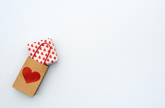 Подарочная коробка дня валентинок с бумажным мини-мешком на сером фоне. копировать пространство