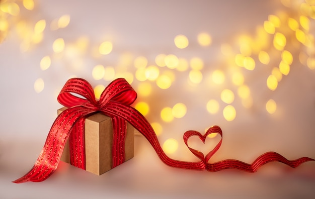 Valentines day gift box with red bow ribbon and heart on bokeh background with copy space