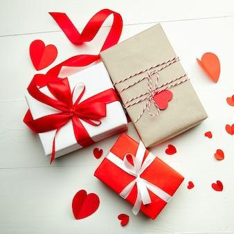 Подарочные коробки на день святого валентина и красные бумажные сердца на белом деревянном фоне