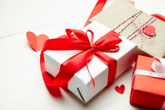 Подарочные коробки на день святого валентина и красные бумажные сердца на белом деревянном столе