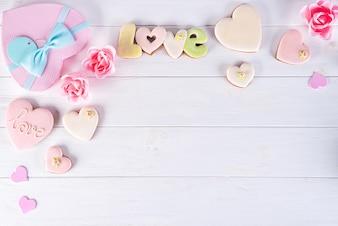Подарочные коробки Дня святого Валентина с печеньями сердца на белой деревянной предпосылке.
