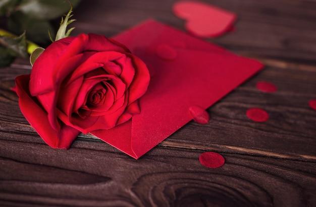 Подарочная карта на день святого валентина в красном конверте и красная роза на деревянном коричневом фоне