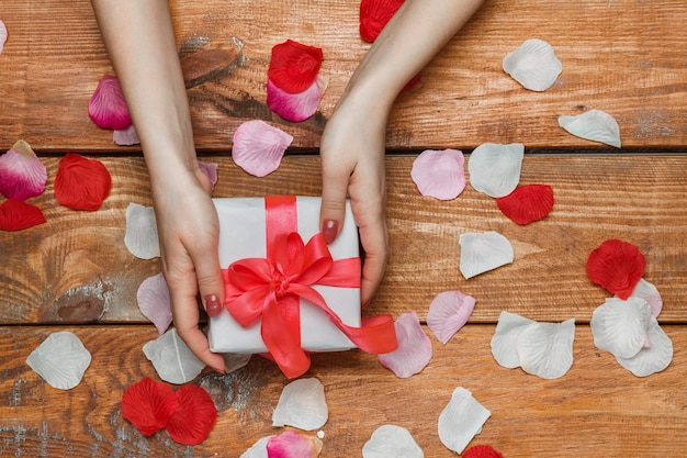 Подарок на день святого валентина в белой коробке и женские руки и лепестки на деревянном фоне