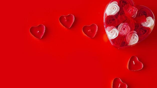 赤い背景の上のバレンタインデーのギフト。赤いリボンで結ばれたハート型のパッケージにたくさんの赤と白のバラ。愛の概念