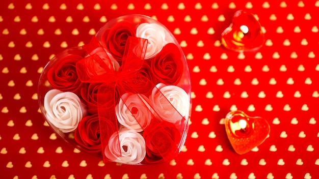 Подарок дня святого валентина на красном фоне. много красных и белых роз в упаковке в форме сердца, перевязанной красной лентой. понятие любви