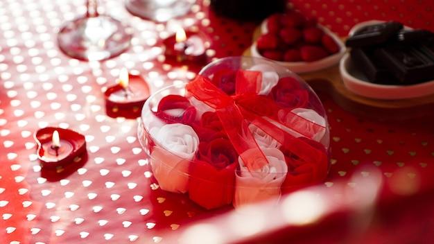 Подарок дня святого валентина на красном праздничном фоне. много красных и белых роз в упаковке в форме сердца, перевязанной красной лентой. концепция ужина