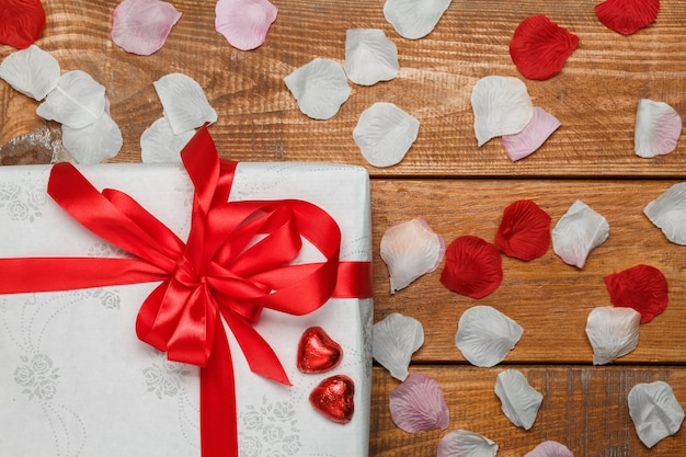 Valentines day gift in white box and hearts and petals on wooden background