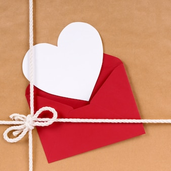 Valentines day gift with white heart shape card, red envelope, brown paper package parcel background