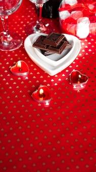 バレンタイン・デー。メガネ、赤いバラ、キャンドル-赤い背景。愛の夕食の概念-垂直写真